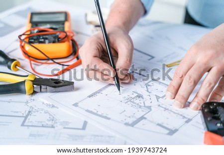 Man repairer making electricity project in house.Repairs planning.Drawing,diagrams,plan of electrification of apartment,building.Devices,accessories,voltmeter,wires,screwdriver,pliers and tape measure Stock photo ©