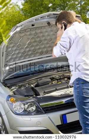 Man repairing a broken car by the road - stock photo