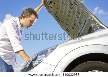 man repairing a broken car on a road