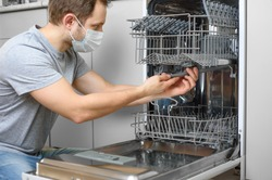 Man repairing a dishwasher with tools