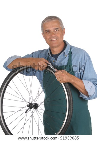 Man Repairing Bicycle isolated over white. Middle aged male holding wrench and leaning on a bicycle wheel that is removed from bike.