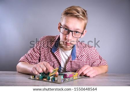 Man repairing broken computer, video card,memory RAM, cooler, processor,hard drive. Young repairer working with screwdriver in service center.teenager  #1550648564