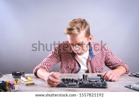 Man repairing broken computer, video card,memory RAM, cooler, processor,hard drive. Young repairer working with screwdriver in service center.teenager