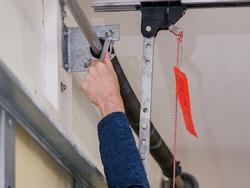 Man repairing electric garage door coiled tension spring. Installing and adjusting overhead garage door opener.