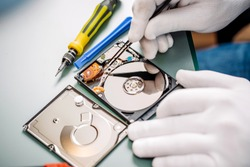 man repairing hard drive in service center. Repairing and fixing service in lab. Electronics repair service concept.