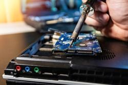 Man repairing hard drive in service center. Repairing and fixing service in lab. Electronics repair service concept. Concept of computer hardware electronic, repairing, upgrade and technology.