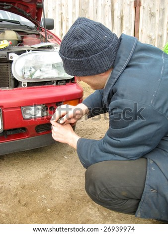 Man, repairing the car fog lights, outdoor #26939974