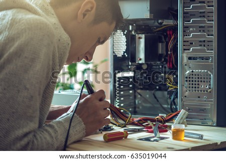 Man repairman is trying to fix using the tools on the computer that is on a workplace in the office. The concept of service electronics and computers.
