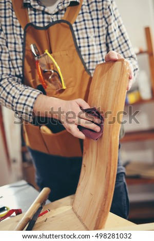 Man repairs a chair in his workshop. #498281032