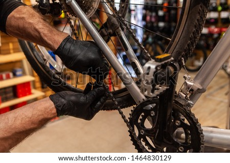 Man repairs bicycle in workshop. A mechanic wearing black gloves is viewed close-up, repairing a chain link of a sports bicycle, blurry foot pedal is viewed in the foreground with copy-space