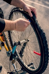 Man repairs punctured bicycle with wheel flank extractors. Tools