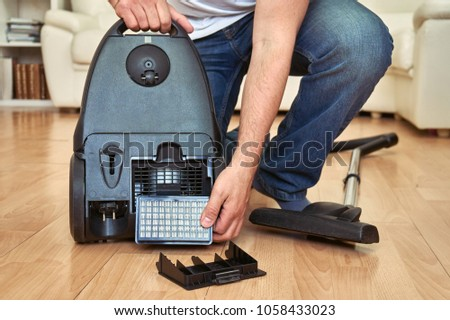 Man replacing an air  filter of a vacuum cleaner at home. #1058433023
