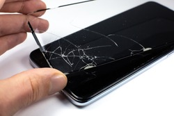 Man replacing the broken tempered glass screen protector for smartphone. Close up.