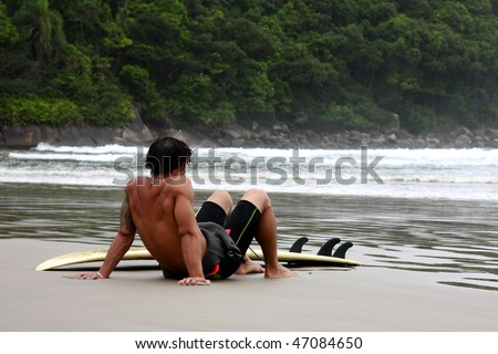 Man resting after surfing on a tropical beach