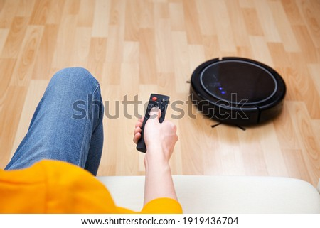 Man resting while robotic vacuum cleaner doing chores, clean work at home. Man controls a robot vacuum cleaner using a remote control. Cleaner robot vacuum cleaner cleans the floor