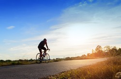 Man ride a bicycle at sun set .The image of cyclist in motion on the background in the evening.