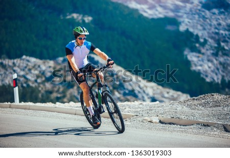 Man ride mountain bike on the road. Sport and active life concept. #1363019303