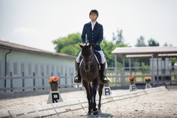 man rider and black stallion horse walking during equestrian dressage competition in summer