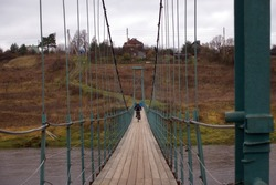 Man rides a bike cross country bike on suspension bridge over river. Moscow region in autumn, Russia.