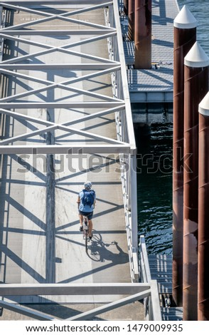 Man rides a bike on a bike path crossing a mobile ramp on a floating dock on a river. The use of a bicycle as the main transport for many enthusiasts has grown from a hobby into vital necessity