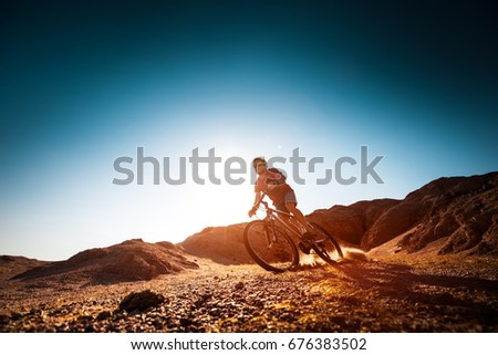 Man rides bicycle in the dry desert terrain