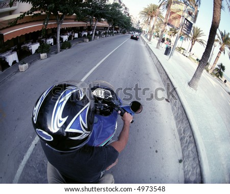 man rides in street on his motorbike, sitges, spain