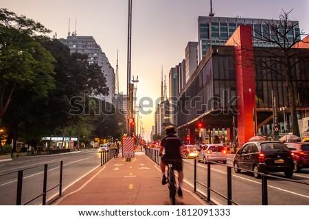 Man riding a bicycle on the Paulista Avenue bike path  Translation: 'Next street. Peixoto Gomide street' Stock photo ©