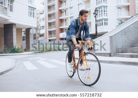 Man riding a bicycle outside. Concentrated young guy using his bike in the courtyard. Urban background