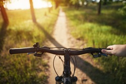 man riding a bike. holding bike handlebar with one hand. summertime outdoor leisure sport activity. first-person view bicycle riding. strong evening sunlight