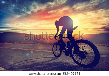 Man riding a bike in high mountains at sunset. Extreme sport, speed, risk, lifestyle.