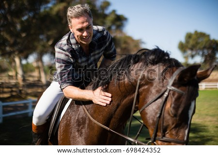 Man riding a horse in the ranch on a sunny day