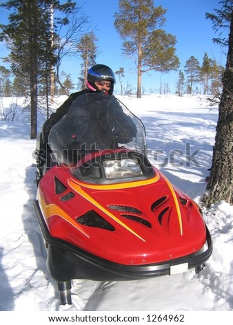 Man riding a red snowmobile - stock photo