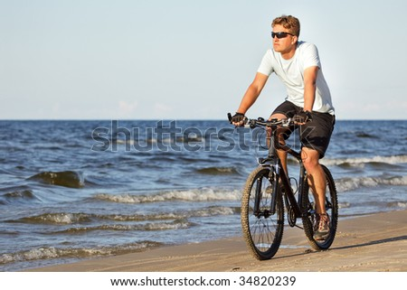 Man riding bicycle in beach along the sea