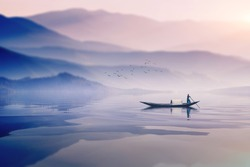 man riding boat in a  foggy winter morning infront of a beautiful  mountain in lake in bangladesh