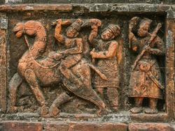 Man riding camel going hunting with servants and bird: intricate terracotta carving at Kantaji aka Kantajew medieval hindu temple in Kantanagar, Dinajpur district, Bangladesh