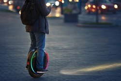 Man riding fast on electric unicycle on city street at night with diode headlights. Mobile portable individual transportation vehicle. Night riding, man on electric mono-wheel riding fast (EUC)