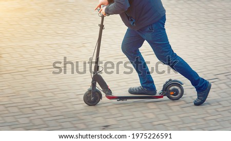 Man riding fast on kick scooter on pavement in the city. Rider pushing off ground and moving down the street, side view. Push off on scooter. Healthy lifestyle, transportation concept ストックフォト ©