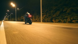 Man riding fast on modern sport motorbike at nighty city street. Motorcyclist racing his motorcycle on empty road. Guy driving bike at dusk. Concept of freedom and adventure. Low angle of view Closeup
