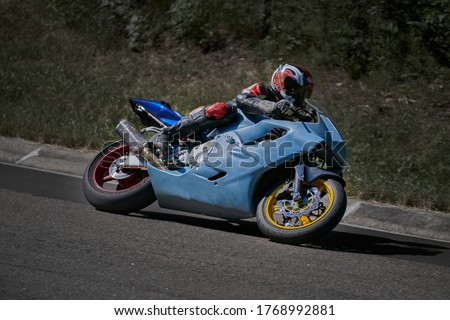 Man riding motorcycle in asphalt road curve with rural,motorcycle practice leaning into a fast corner on track. Sport Biker Racing on Road Stock photo ©