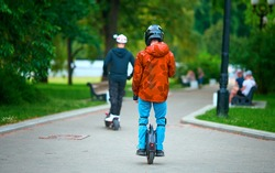 Man riding on unicycle in protective gear through public park. Young man with helmet and protective equipment rides on electric mono wheel in park on summer day. Urban individual transport