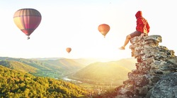 Man risk at the edge. Tourist looking at baloons. The great tourist attraction of best places to fly with hot air balloons. Adventure concept. View into during sunset valley with lots of balloons