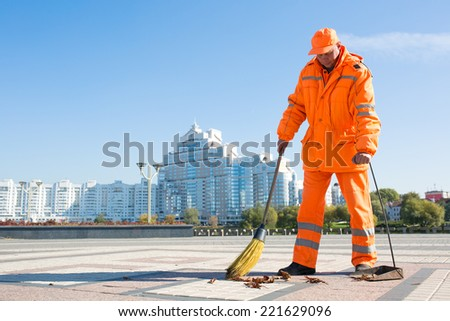 Man road sweeper caretaker cleaning city street with broom tool