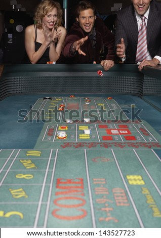 Man rolling the dice at a gambling table in a casino