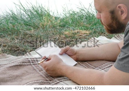 Man romantic writing in his notebook in forest at lake #472102666