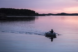Man rowing a boat in sunset