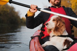 Man rowing a canoe with his spaniel dog, sunny autumn weather. Going kayak boating with dogs on the river, active pets, happy dog and owner on an adventure
