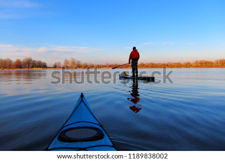 Man rowing with a paddle on the stand up paddle board (paddleboard, SUP) in the Danube river at calm cold winter evening. View from bow of blue kayak Stock fotó ©