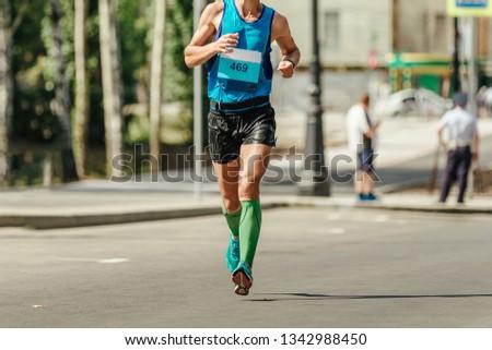 f9b30bc70 man runner in compression socks running marathon in hot weather