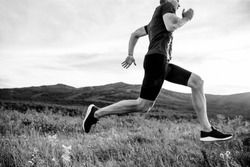 man runner running on background of mountain and sky black and white photo