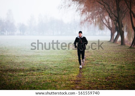 Man running during foggy weather at winter or autumn morning.